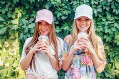 Vrouwen met dranken dichtbij struik stock fotografie