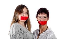 2 vrouwen met een zelfklevende strook voor de mond stock fotografie