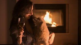 Vrouwen met haar hondzitting dichtbij open haard en het drinken wijn stock video