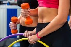 Vrouwen met naakte buik werkende domoren en hoepel bij gymnastiek Stock Foto