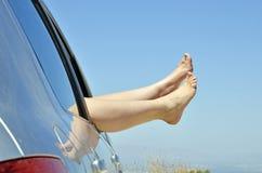 Vrouwen met naakte voeten uit het venster van de auto Stock Fotografie
