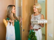 Vrouwen met zakken voedsel dichtbij deur Stock Fotografie