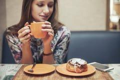 Vrouwen mooi model in de koffiewinkel met gebakjes en telefoon stock foto's