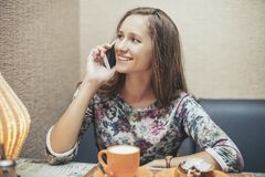 Vrouwen mooi model in de koffiewinkel met gebakjes en telefoon stock afbeelding