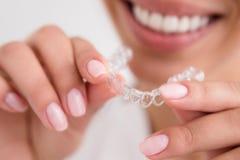 Vrouwen mooie glimlach die een transparante mondwacht houden stock foto