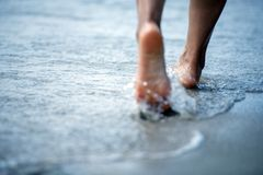 Vrouwen naakte voet die op het de zomerstrand lopen sluit omhoog been van het jonge vrouw lopen langs golf van zeewater en zand o stock afbeelding