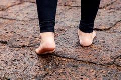 Vrouwen naakte voeten die op natte rotsachtige bestrating lopen Royalty-vrije Stock Foto