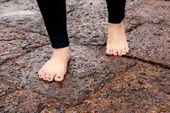 Vrouwen naakte voeten die op natte rotsachtige bestrating lopen Stock Foto's