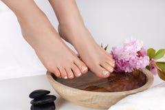 Vrouwen naakte voeten met Franse pedicure in kuuroordsalon met houten kom en roze bloem en steendecoratie stock foto's