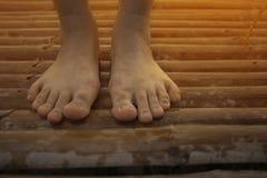 Vrouwen naakte voeten op houten vloer, bamboe royalty-vrije stock afbeeldingen