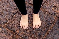 Vrouwen naakte voeten op natte rotsachtige bestrating Royalty-vrije Stock Fotografie