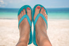 Vrouwen naakte zandige voeten met blauwe wipschakelaars, strand en overzees Stock Fotografie