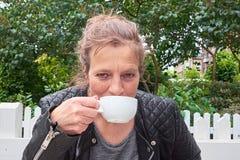 Vrouwen nippende koffie in een tuin Stock Afbeelding