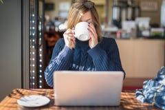vrouwen nippende mok van chai die laptop computer bekijken Stock Afbeelding