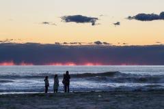 Vrouwen op de oever bij zonsondergang royalty-vrije stock afbeeldingen