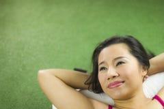 Vrouwen op het groene gras liggen, een mooie en stellende glimlach, Thaise vrouw die op groen gras bepalen royalty-vrije stock fotografie