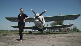 Vrouwen proefportret voor vliegtuigbommenwerper in een zwarte combo die zich voor een reusachtige luchtpropeller bevinden stock videobeelden