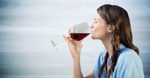 Vrouwen proevende wijn tegen onscherp blauw houten paneel royalty-vrije stock afbeeldingen