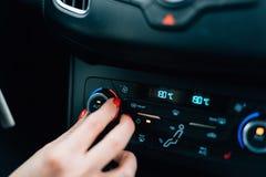 Vrouwen regelende temperatuur op de voorwaarde van de autolucht royalty-vrije stock afbeeldingen