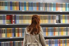 Vrouwen rode haired achtermening voor boekenplanken stock foto