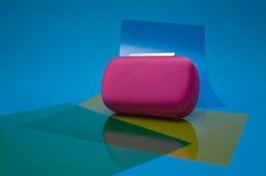 Vrouwen roze zak op blauwe achtergrond en plastic bezinningen Stock Foto's