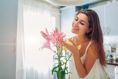 Vrouwen ruikend boeket van lelies Huisvrouw die van decor en binnenland van keuken genieten Zoet Huis royalty-vrije stock afbeeldingen