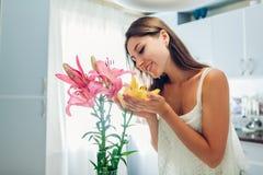 Vrouwen ruikend boeket van lelies Huisvrouw die van decor en binnenland van keuken genieten Zoet Huis royalty-vrije stock foto
