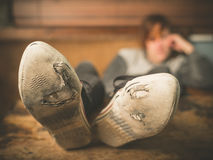 Vrouwen rustende voeten op lijst Stock Foto