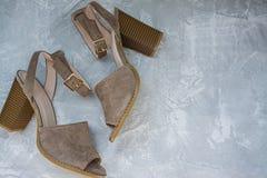 Vrouwen` s beige sandals De zomerschoeisel Lichte achtergrond Achtergrond onder het beton Ruimte voor tekst stock foto