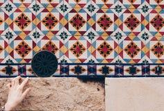 Vrouwen` s hand die een detail van de Kleurrijke voorgevels met Traditionele decoratie richten - Lissabon, Portugal stock afbeelding