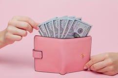 Vrouwen` s hand die geld verwijderen uit portefeuille op de roze achtergrond met exemplaarruimte stock fotografie