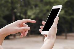Vrouwen` s hand die slimme telefoon houden stock foto's