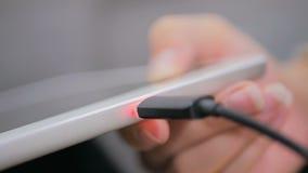 Vrouwen` s hand die zwarte bliksem het laden kabel stoppen in de digitale tablet van PC stock videobeelden