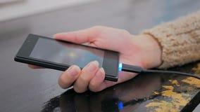 Vrouwen` s hand die zwarte bliksem het laden kabel stopt in smartphone stock video
