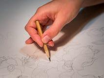 Vrouwen` s hand een potlood en trekken die bloemen op watercolo houden Royalty-vrije Stock Afbeeldingen