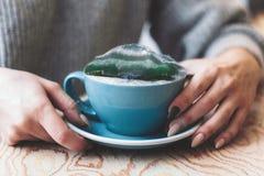 Vrouwen` s hand met overzees onweer in koffiekop stock afbeeldingen
