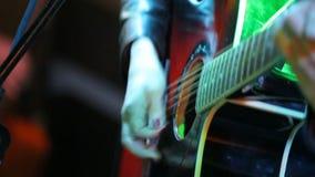 Vrouwen` s handen die akoestische gitaar op overleg spelen stock footage