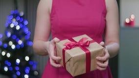 Vrouwen` s Handen die een Kerstmisgift houden stock foto's