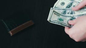 Vrouwen` s handen die een ventilator van honderd dollarsrekeningen en tellingen houden stock videobeelden