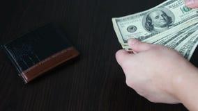 Vrouwen` s handen die een ventilator van honderd dollarsrekeningen en tellingen houden stock video