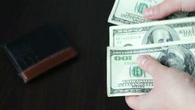 Vrouwen` s handen die een ventilator van honderd dollarsrekeningen en tellingen houden stock footage