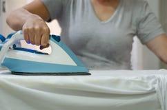 Vrouwen` s handen die heet ijzer houden, die kleren, ondiepe diepte o stomen royalty-vrije stock foto's