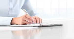 Vrouwen` s handen die op blad in een klembord met een pen schrijven, isola Stock Foto's