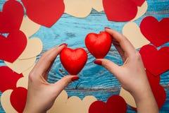 Vrouwen` s handen die rode de dagachtergrond houden van hartenvalentijnskaarten Stock Fotografie