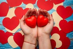 Vrouwen` s handen die rode de dagachtergrond houden van hartenvalentijnskaarten Royalty-vrije Stock Fotografie