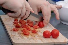 Vrouwen` s handen die tomaat, achter verse groenten snijden stock foto