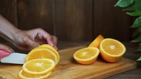 Vrouwen` s handen die verse sinaasappel op keuken snijden stock videobeelden