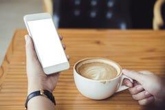 Vrouwen` s handen die witte mobiele telefoon met het lege scherm en witte koffiekop houden van hete latte op houten lijst in mode Stock Foto