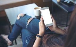 Vrouwen` s handen die witte mobiele telefoon met het lege scherm op dij in koffie houden Stock Foto's