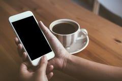 Vrouwen` s handen die witte mobiele telefoon met het lege zwarte scherm en witte koffiekoppen in moderne zolderkoffie houden Royalty-vrije Stock Afbeelding